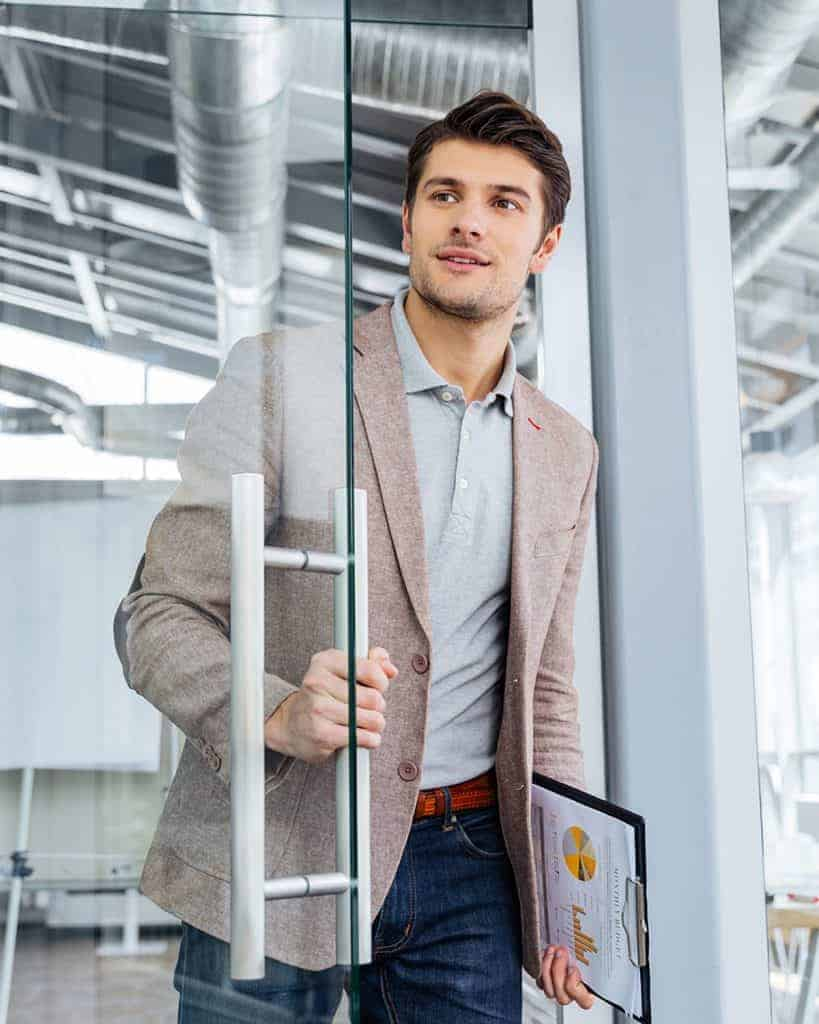 Handsome young businessman with clipboard entering the door in o